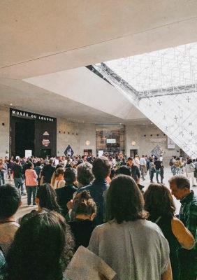 Label Experience : Prisse de vue de l'intérieur du musée avec la pyramide principale et ses visiteurs, lieu proche du pop-up store de l'enseigne « Pyramid » au Carrousel du Louvre.