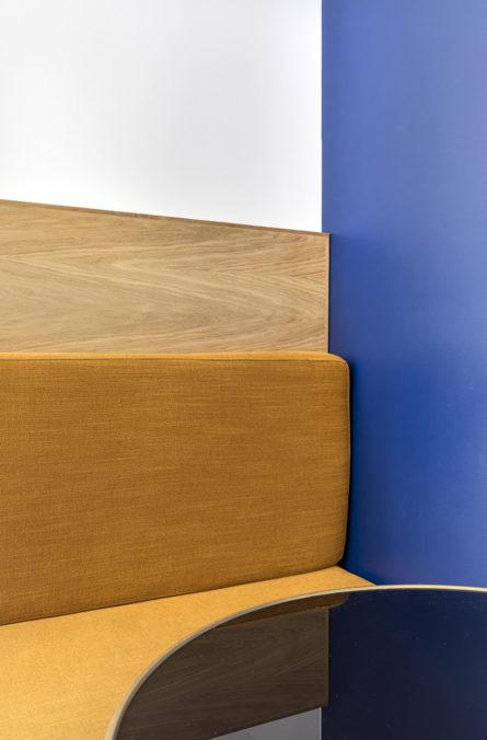 Label Experience: Focus banquette moutarde/bois, mur bleu et table bistrot dans les bureaux de « Alter Solutions » à Versailles.