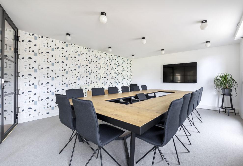 Label Experience: Grande salle de réunion avec table en bois massif connectée dans les bureaux de « Alter Solutions » à Versailles.