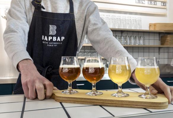 Label Experience: Présentation de différentes bières sur planche de bois au comptoir du bar « BAP BAP » à Paris