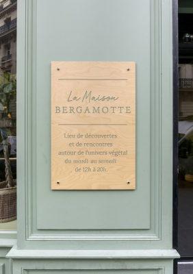 Label Experience: Enseigne extérieure métallique sur fond vert-gris de la « Maison Bergamotte » à Paris.