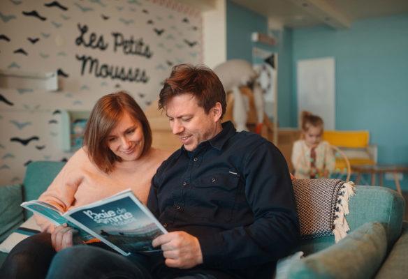 Label Experience : proche de la bibliothèque, des parents en pleine lecture dans le hall d'accueil du Pierre & Vacances au Crotoy