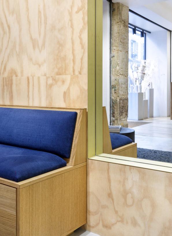 Label Experience: Focus sur banquette, mur en bois et miroir de la boutique « Bonne Gueule » à Paris.