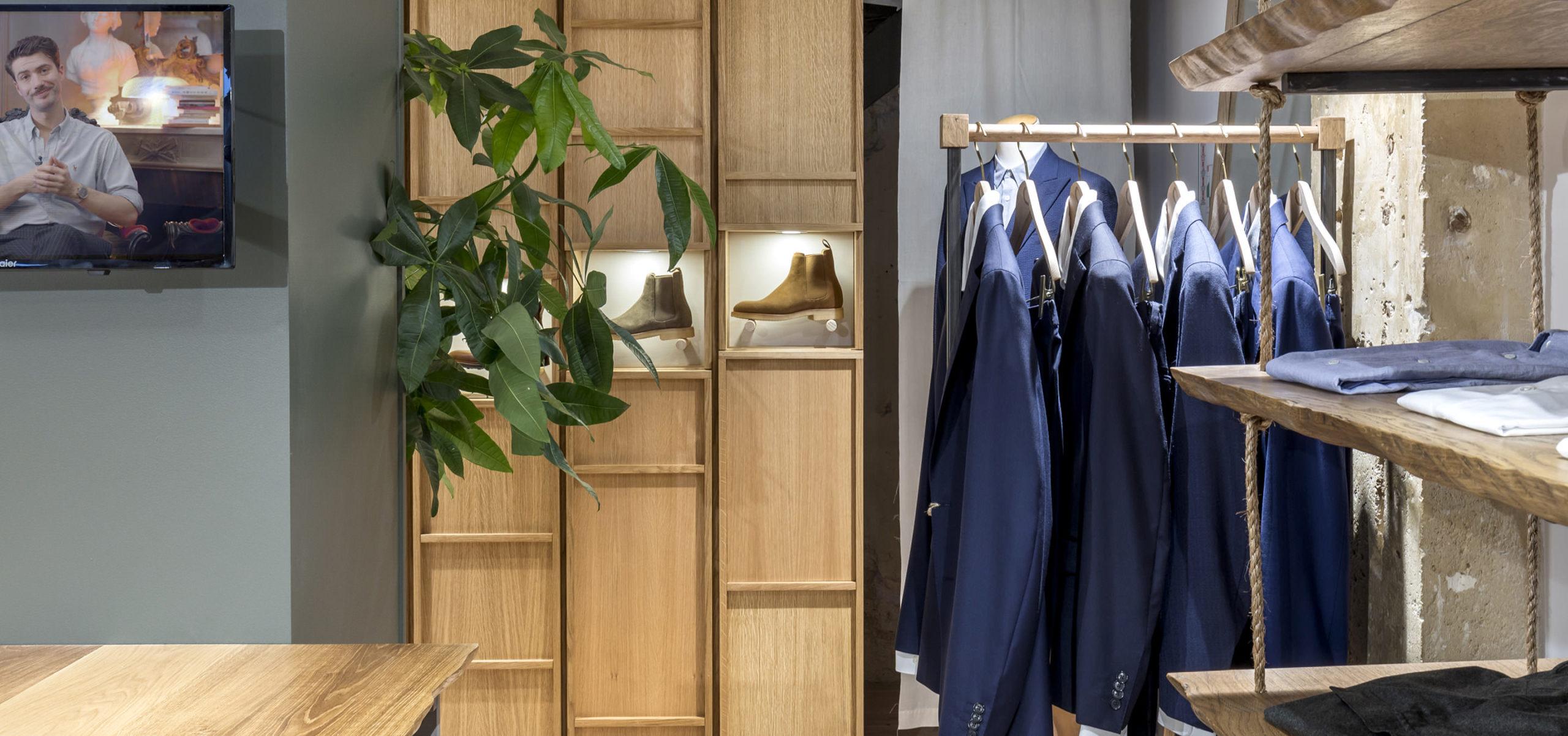 Label Experience: Bottines homme et costumes à côté d'une plante verte de la boutique « Bonne Gueule » à Paris.
