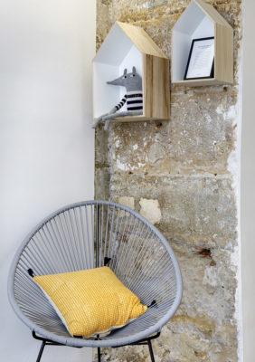 Label Experience: Focus fauteuil et étagères en forme de maison sur mur de pierre du pop-up « émoi émoi » à Paris.