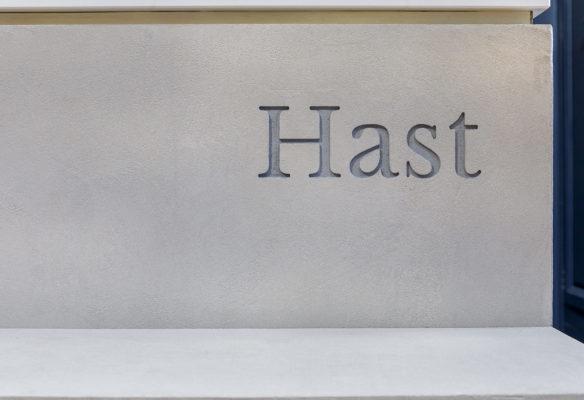 Label Expérience: Zoom du logo en gris de la boutique « Hast » aux Batignolles.