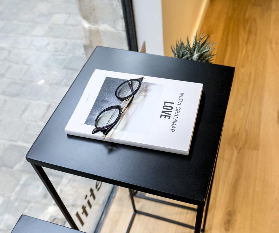 Label Experience : une paire de lunettes Le Petit Lunetier posé sur une petite table dans la boutique à Lyon