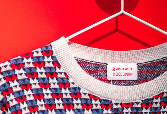 Label Experience: Focus pull sur cintre devant mur rouge flash du pop-up store « Montagut » à Paris.