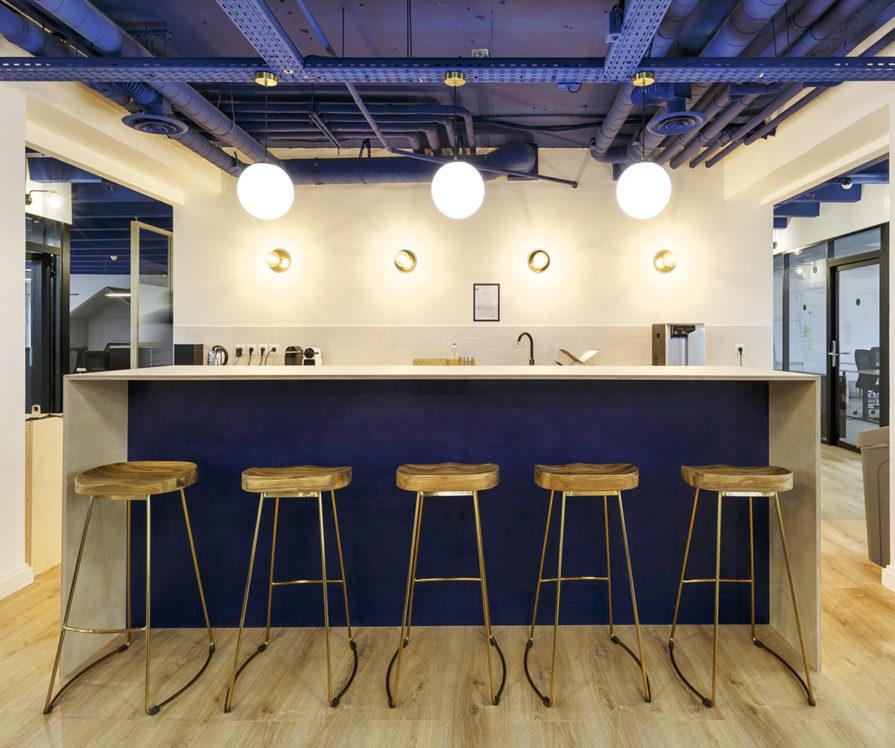 Label Experience: Coin bar et chaises hautes aux couleurs bleu de l'espace coworking « Morning » Monceau à Paris.