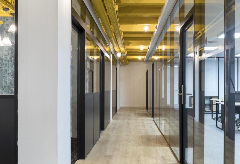 Label Experience: Long couloir aux cloisons vitrées de l'espace coworking « Morning » Monceau à Paris.