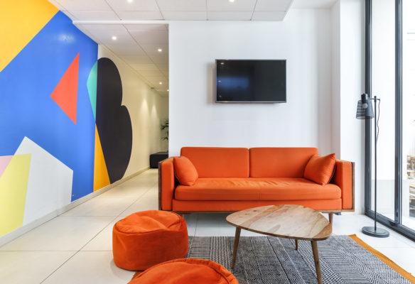 Label Experience: Espace détente avec canapés orange du nouveau espace coworking de « Schoolab » à Saint-Lazare.