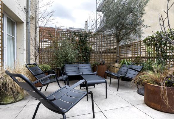 Label Experience: Terrasse avec chaises noir du bureau « Smallable » à Paris.