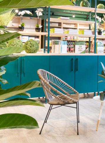 Label Experience: Focus sur chaise en osier, plantes et placards bleu canard de la boutique « Truffaut » à Boulogne.