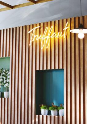 Label Experience: Focus sur bois et logo en neon de la boutique « Truffaut » à Boulogne.