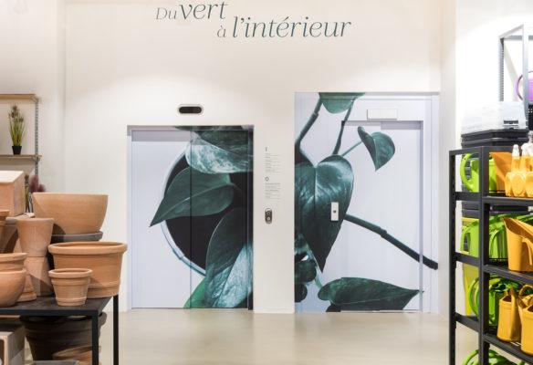 Label Experience: Ascenseur et porte avec décoration de feuilles de la boutique « Truffaut » à Boulogne.