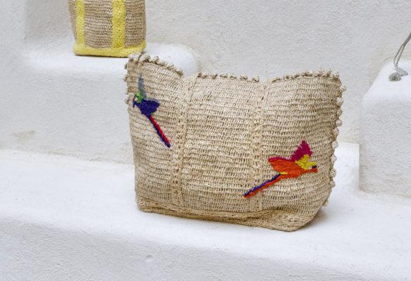 Label Experience: Focus sur sac de voyage en rotin avec dessins de perroquets de la nouvelle collection de Vanessa Bruno Rio dans les Galeries de la Fayette.
