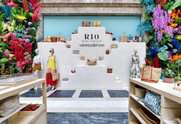 Label Experience: Vue globale de l'exposition de sacs sur escalier blanc pour Vanessa Bruno Rio dans les Galeries de la Fayette.