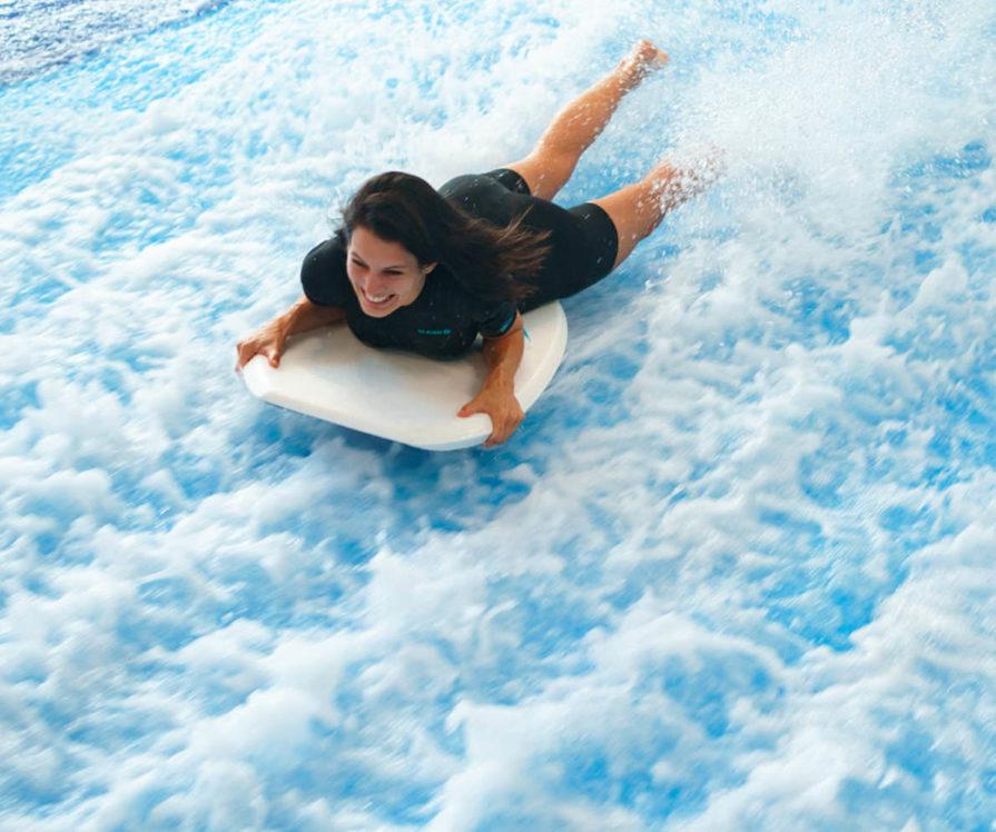 Label Experience: Surfeuse sur planche dans la piscine avec des vagues artificielles au tiers-lieu « The Wave Factory » à Lisbonne.