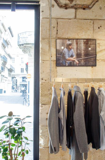 Label Experience: Costumes et cadre sur mur en pierre de la boutique « Bonne Gueule » à Bordeaux.