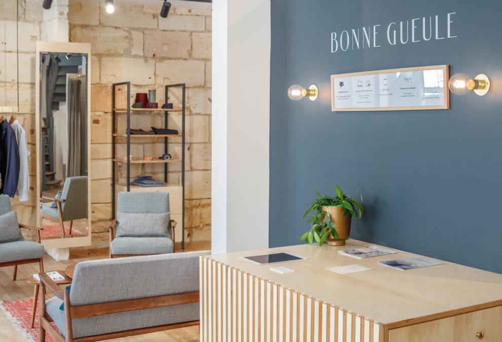 Label Experience: Mobilier en bois devant mur bleu de la boutique « Bonne Gueule » à Bordeaux.
