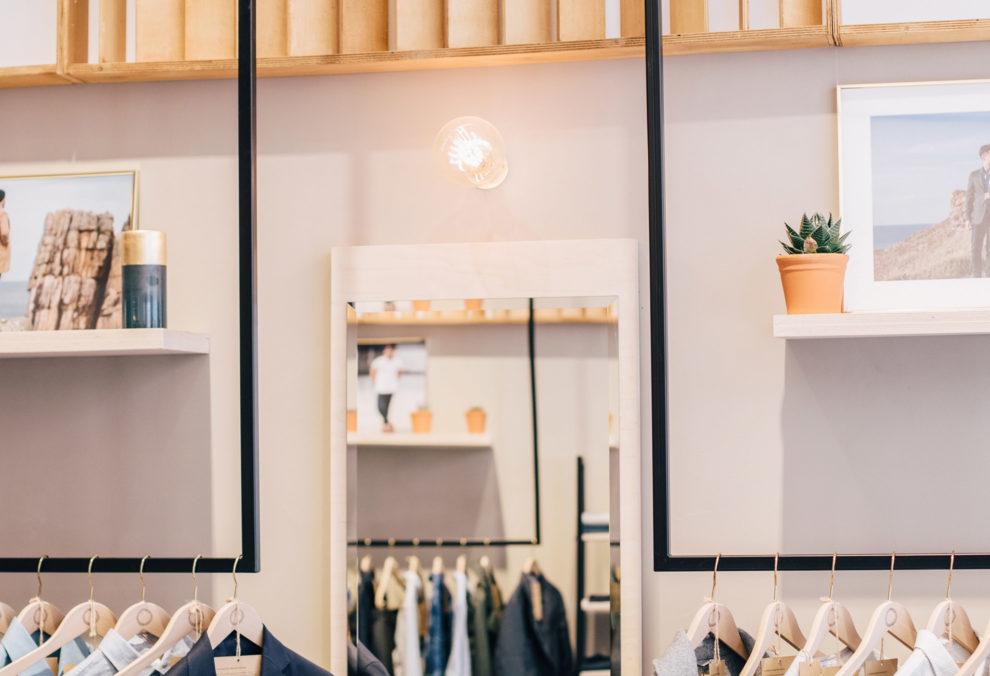 Label Experience : zoom sur des portants de vêtements dans l'espace vente de la boutique BonneGueule à Lyon