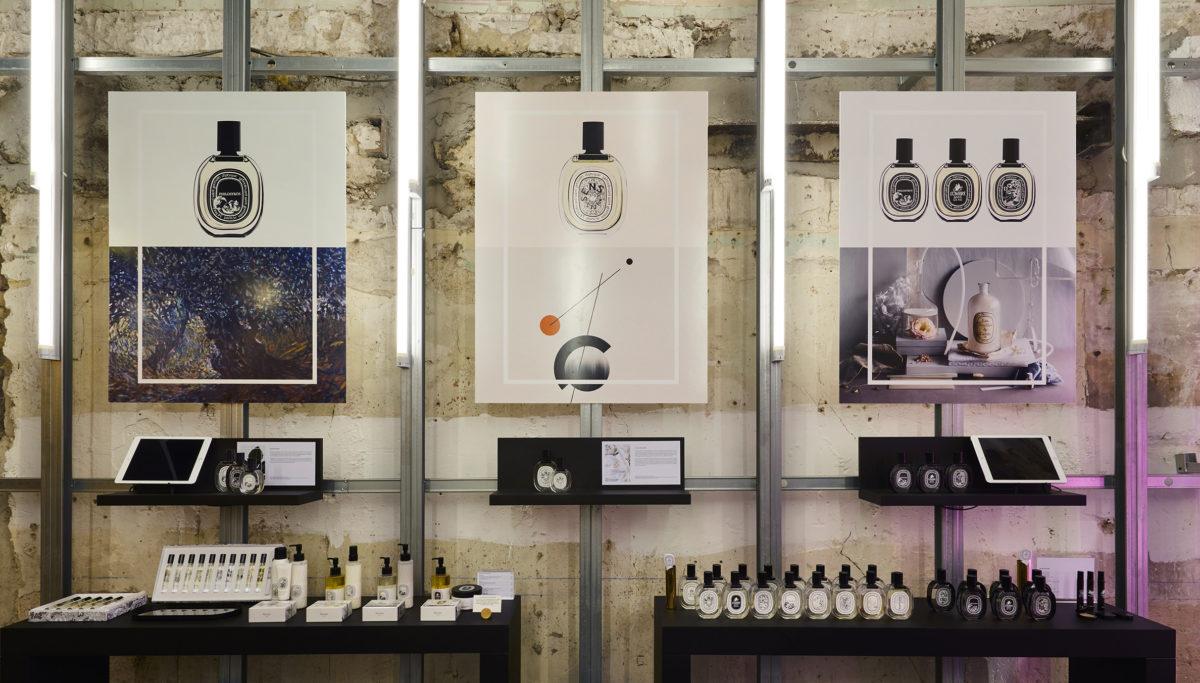 Label Experience: Trois affiches et produits cosmétiques devant mur de pierre du pop-up store de Diptyque à St Honoré, Paris.