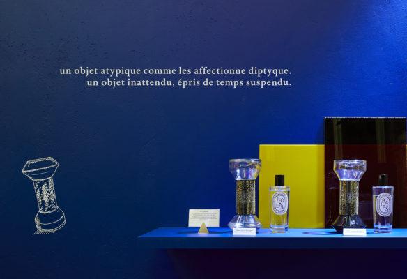Label Experience: Produits sur présentoir devant mur bleu avec citation du pop-up store « Diptyque » rue St Honoré à Paris.