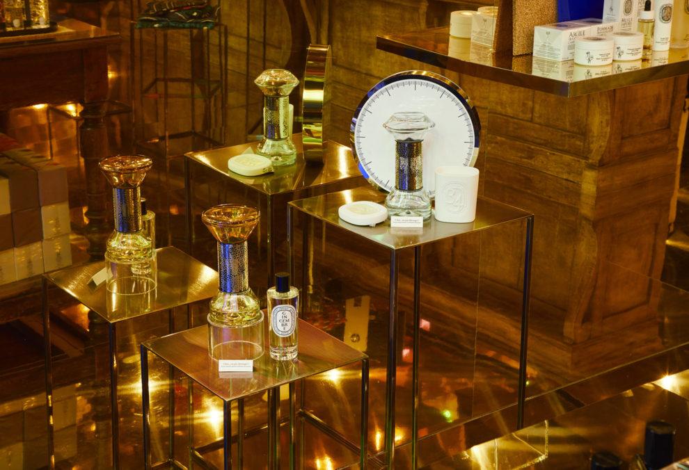 Label Experience: Produits sur présentoirs dorée du pop-up store « Diptyque » rue St Honoré à Paris.