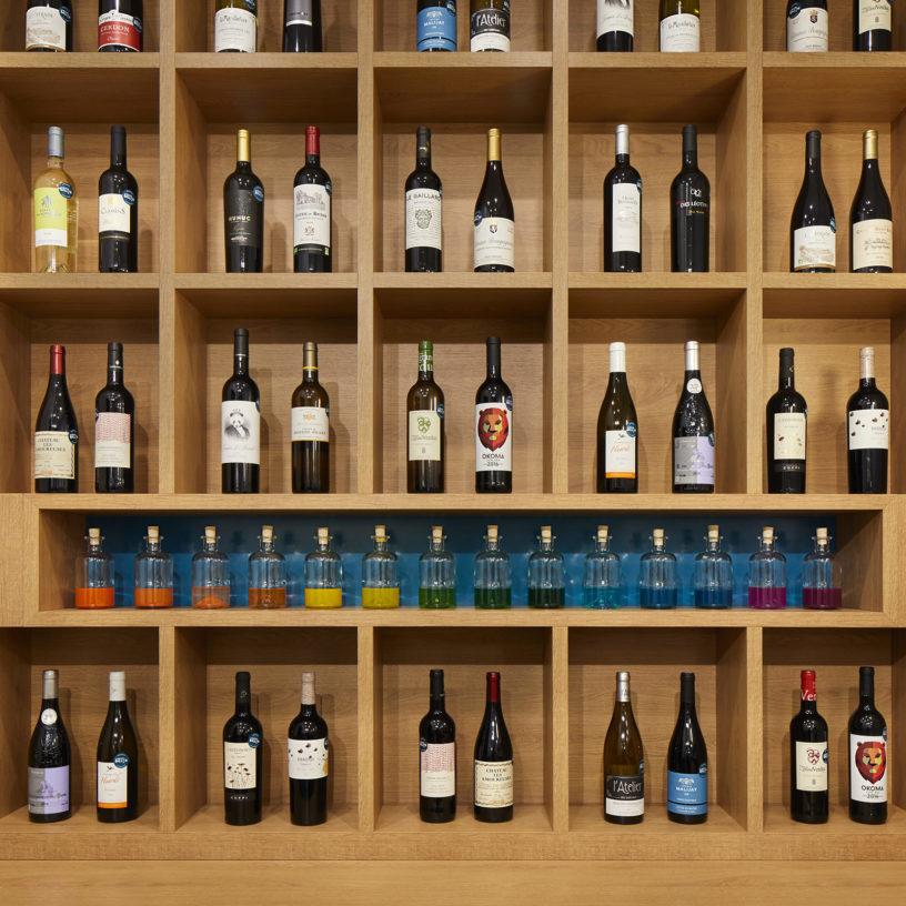 Label Experience : zoom sur une étagère en bois contenant des bouteilles de vin en vente dans la boutique Le Petit Ballon à Paris