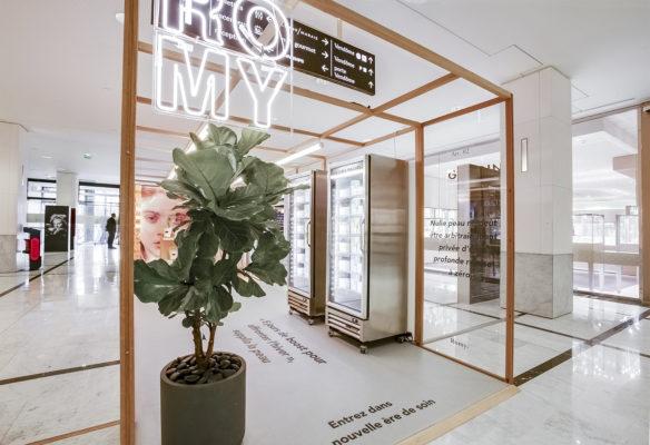 Label Experience: Entrée de l'espace avec logo en neon, plante et réfrigérateurs métalliques du pop-up store « Romy » au Chesnay.