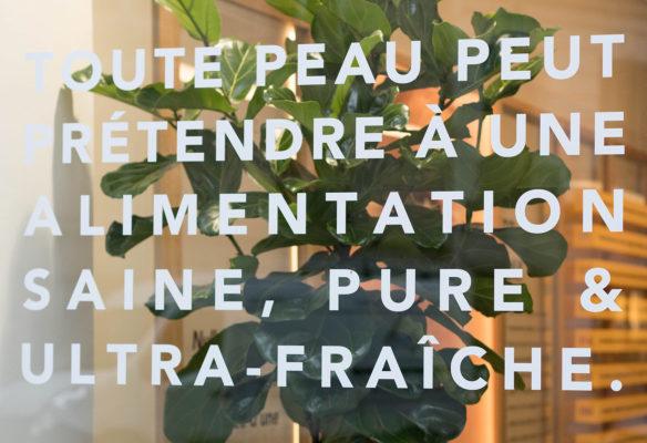 Label Experience: Focus lettres blanches sur baie vitrée du pop-up store « Romy » à Paris.