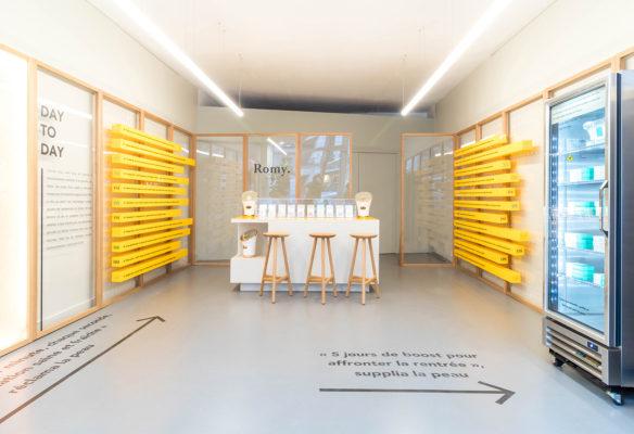 Label Experience: Coin bar et tabourets, avec décoration murale jaune du pop-up store « Romy » à Paris.