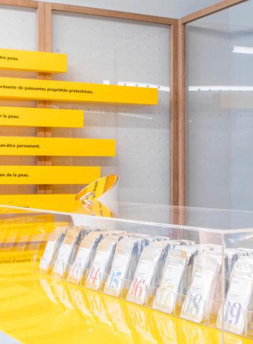 Label Experience: Échantillons cosmétiques et décoration murale jaune du pop-up store « Romy » à Paris.