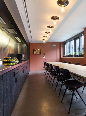 Label Experience: Grande table de réunion avec cuisine ouverte et durs terracotta du bureau « Smallable » à Paris.