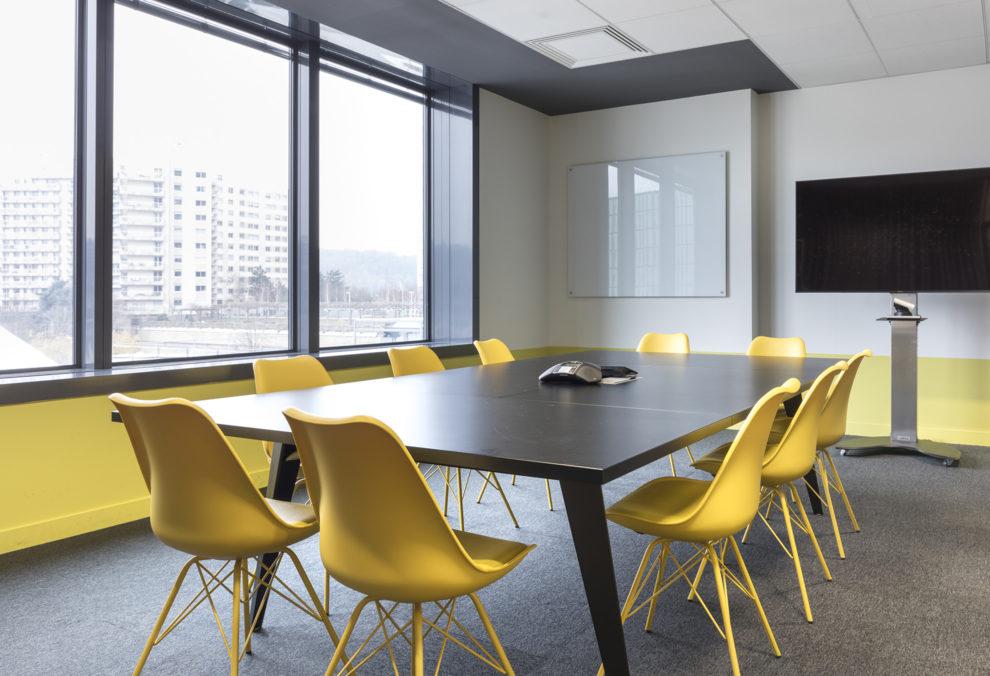 Label Experience: Salle de réunion avec chaises jaunes dans les nouveaux bureaux de « Sodexo » au Social Hub.