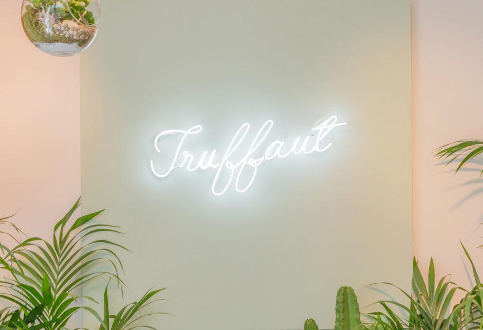 Label Experience: logo de l'enseigne Truffaut en neon et entre des plantes dans son pop-up store à Paris.